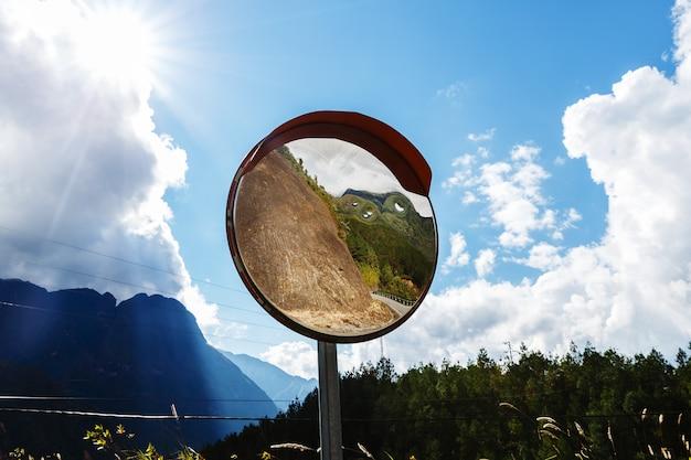 Reflexos da estrada no espelho de tráfego para a segurança do tráfego. espelho de trânsito