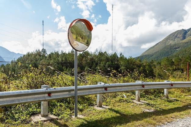 Reflexos da estrada no espelho de tráfego para a segurança do tráfego. estrada de montanha espelho de tráfego, vietname