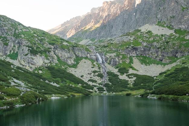 Reflexos nas águas calmas do lago, cachoeira e montanhas ao pôr do sol.