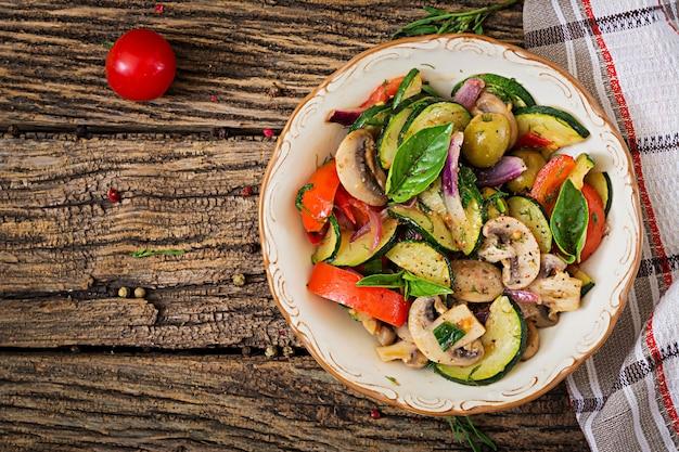 Refogue com cogumelos, abobrinha, tomate, cebola e azeitonas. ensopado de legumes.