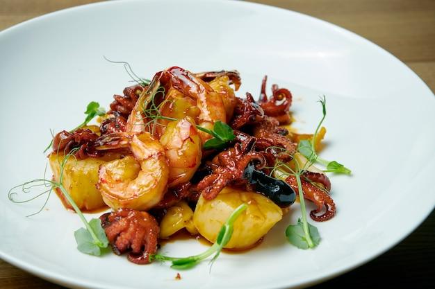 Refogue de frutos do mar: vieiras, polvo e camarão tigre em um prato branco sobre uma mesa de madeira. jantar saboroso. feche acima da vista.