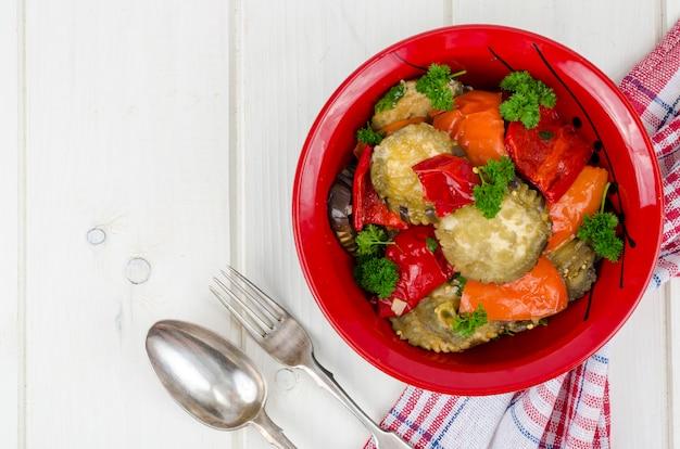 Refogue legumes com berinjela em placa vermelha