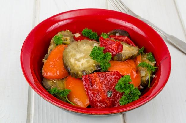 Refogue legumes com berinjela no prato vermelho, comida vegetariana