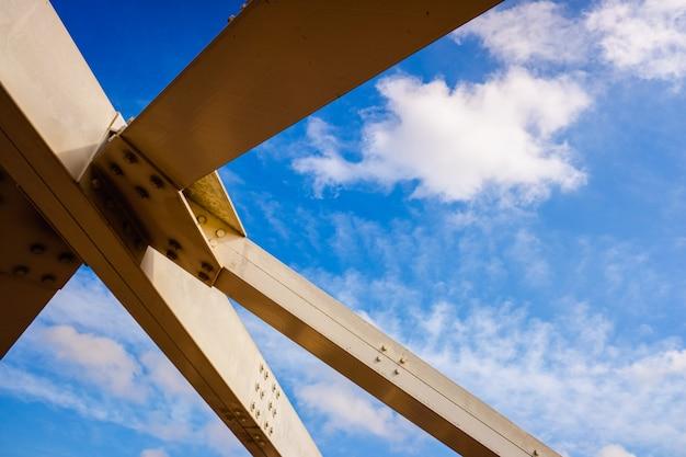 Reforço da estrutura metálica de uma ponte, com vigas de aço branco.