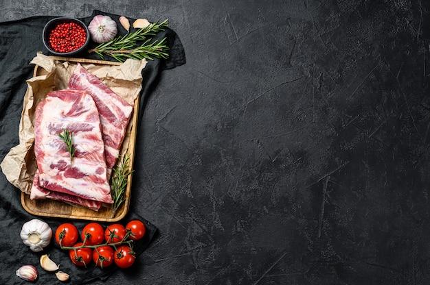 Reforços de carne de porco crus frescos com alecrim e alho em uma tigela de madeira.