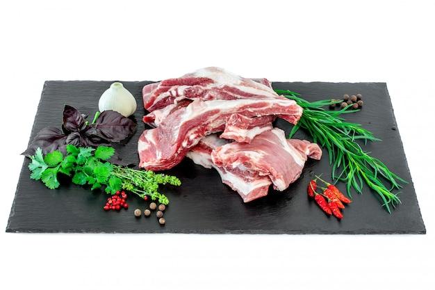 Reforços e condimentos de carne de porco crus apresentados em uma placa de corte de pedra preta.