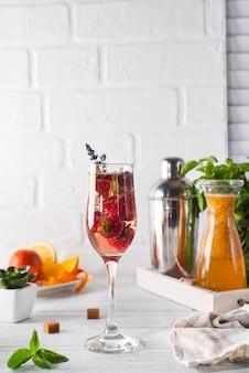 Refrescante cocktail com champanhe e cranberry com gelo, gengibre e lavanda na madeira
