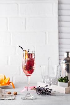 Refrescante cocktail com champanhe e morangos, gelo e lavanda em fundo de madeira