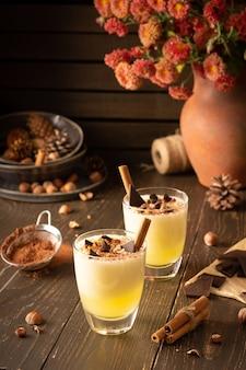 Refrescante e delicioso smoothie de melão com canela, avelãs e chocolate, vaso de crisântemos e copos de smoothie no fundo de madeira