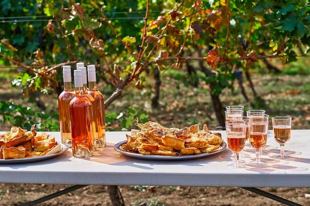 Refrescante vinho rosa na taça, com pastéis sobre a mesa, no cenário de um vinhedo