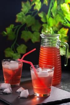 Refrescantes refrigerantes de frutas de verão em um prato preto com plantas atrás
