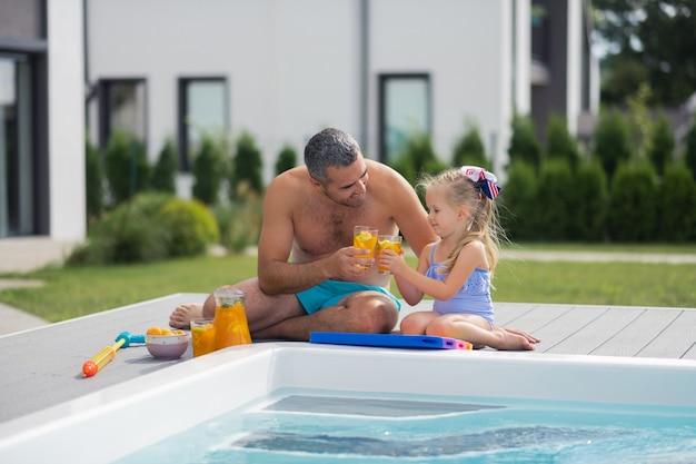 Refrigerando perto da piscina. pai e filha bebendo suco enquanto relaxam perto da piscina no fim de semana