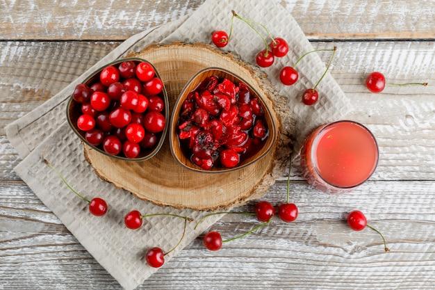 Refrigerante com cerejas, geléia, placa de madeira em um jarro na toalha de madeira e cozinha.