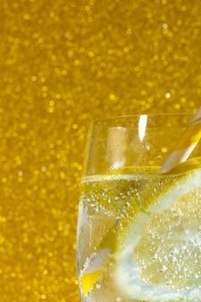 Refrigerante com limão no fundo dourado