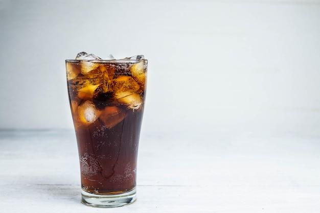 Refrigerante de cola em um copo em uma mesa branca