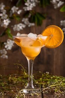 Refrigerante de fruta laranja com gelo em uma superfície de madeira com flores