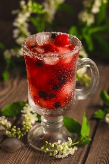 Refrigerante de frutas vermelhas com gelo em uma superfície de madeira com flores