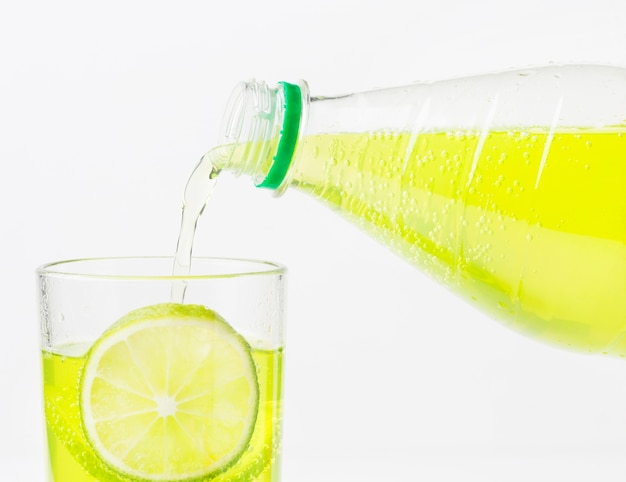Refrigerante sendo derramado em um copo com limão
