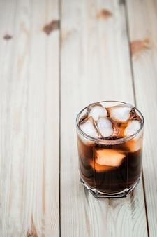 Refrigerantes. copo de cola com cubos de gelo em uma mesa de madeira