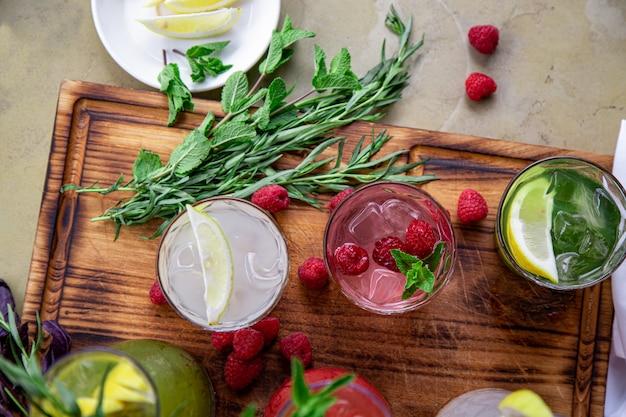 Refrigerantes de verão, um conjunto de limonadas. limonadas em jarras sobre a mesa, cujos ingredientes são feitos, estão dispostos ao redor.