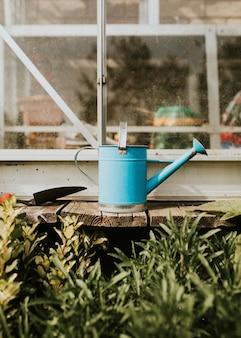 Regador azul na mesa de madeira rústica