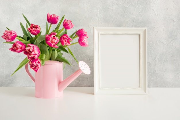 Regador decorativo com tulipas cor de rosa.