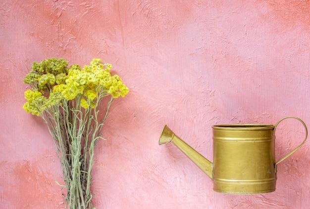 Regador e um buquê de flores. flores. conceito mínimo.
