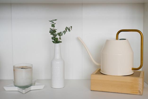 Regador vintage, vaso branco com raminhos de eucalipto e uma vela na prateleira. decoração escandinava em casa