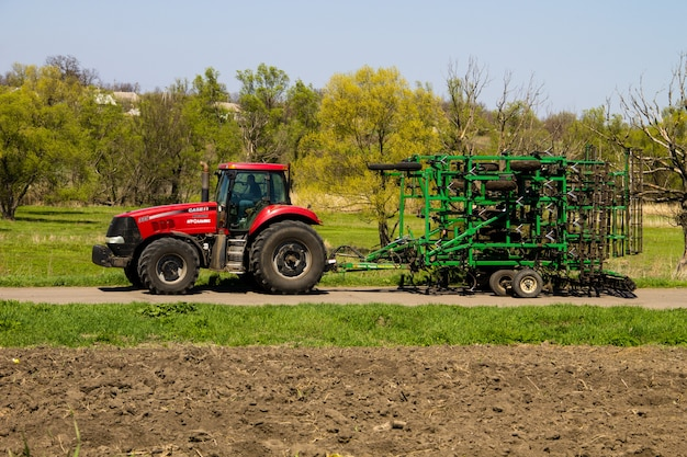Região de kirovograd, ucrânia - 26 de abril de 2017: trator com cultivador na estrada rural