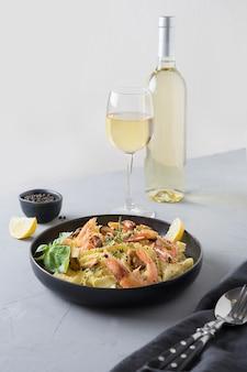 Reginelle de massa com frutos do mar, camarões, mexilhões em chapa preta na mesa de pedra cinza, close-up. prato tradicional em restaurante italiano.