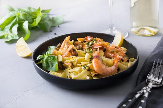 Reginelle de massa com frutos do mar, camarões, mexilhões na mesa de pedra cinza, close-up. prato tradicional em restaurante italiano.