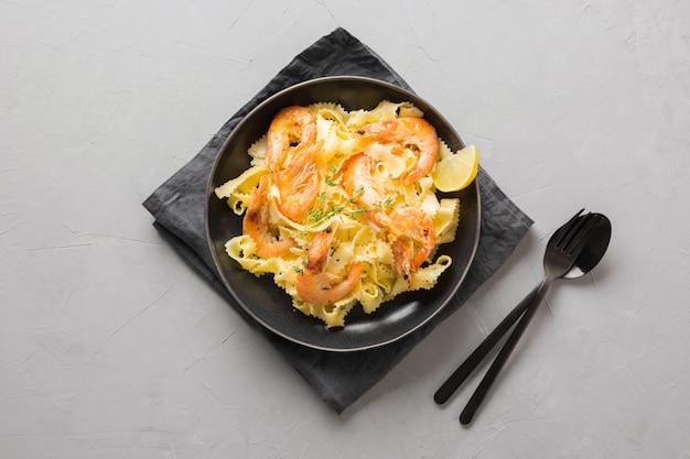 Reginette de massa com frutos do mar, camarões, mexilhões placa preta na mesa de pedra cinza, close-up. prato tradicional em restaurante italiano.