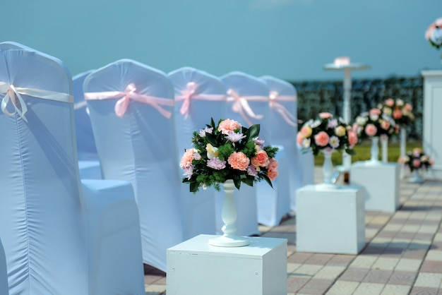Registro de saída dos noivos, cerimônia de casamento a céu aberto. assentos convidados. fileiras de cadeiras com capas brancas, close-up.