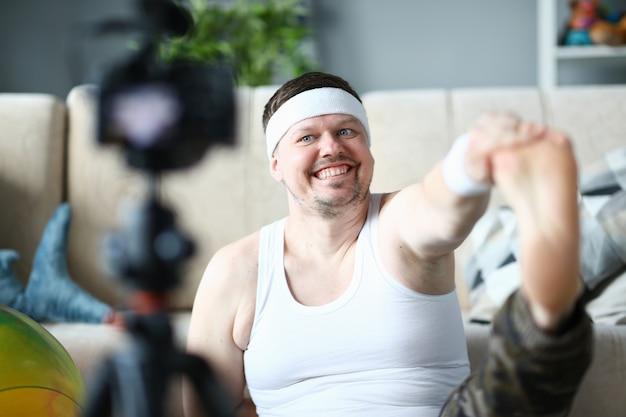 Registro de vlogger feliz que estica o exercício na câmera