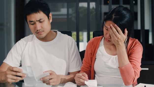 Registros asiáticos grávidos novos dos pares das receitas e despesas em casa. mãe preocupada, séria, estresse enquanto registra orçamento, imposto, documento financeiro, trabalhando na sala de estar em casa.