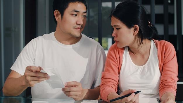 Registros asiáticos grávidos novos dos pares das receitas e despesas em casa. mamãe e papai felizes usando o orçamento recorde de laptop, impostos, documento financeiro, comércio eletrônico, trabalhando na sala de estar em casa.