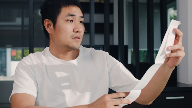 Registros asiáticos novos do homem de negócio das receitas e despesas em casa. masculino preocupado, sério, estresse enquanto estiver usando o orçamento recorde de laptop, imposto, documento financeiro, trabalhando na sala de estar em casa.