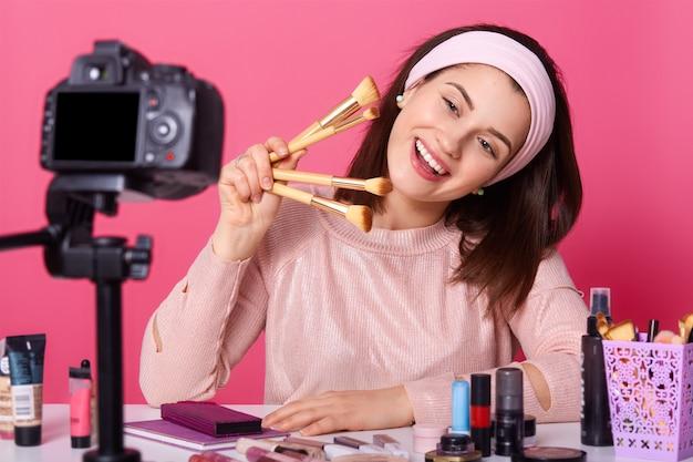 Registros positivos de esteticista feminina compõem o vídeo tutorial, seguram pincéis cosméticos, inclinam a cabeça do prazer, anuncia cosméticos,