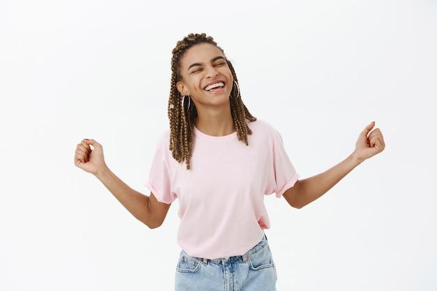 Regozijando-se feliz mulher afro-americana dançando e sorrindo feliz, triunfando