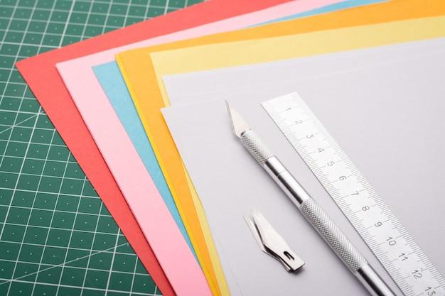 Régua, bisturi e kit de lâminas em papéis coloridos em cima da mesa
