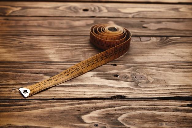 Régua de alfaiate vintage enrolada isolada em uma mesa de madeira rústica close-up