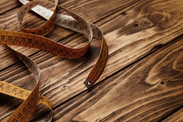 Régua de alfaiate vintage isolada em mesa de madeira rústica