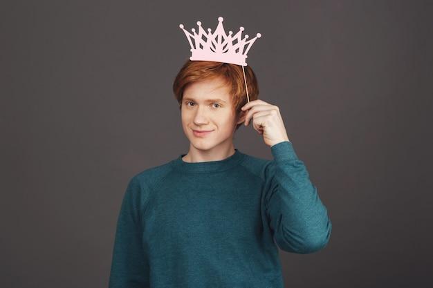 Rei aspirante. feche acima do gengibre adolescente masculino novo bonito na camisola verde à moda que dobra a coroa de papel na vara, com expressão autoconfiante.