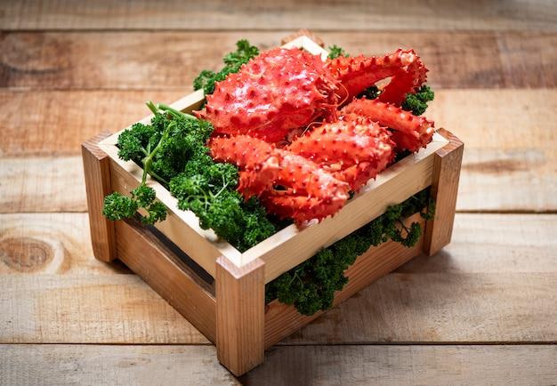 Rei do alasca caranguejo cozido vapor ou marisco cozido em salsa verde encaracolado em caixa de madeira com madeira - hokkaido caranguejo vermelho fresco