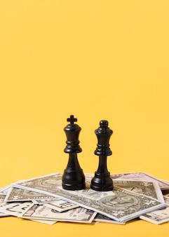Rei e rainha peças de xadrez em pé na pilha de dinheiro