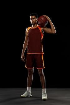 Rei. jovem proposital jogador de basquete afro-americano treinando, praticando em ação, movimento isolado no fundo preto. conceito de esporte, movimento, energia e estilo de vida dinâmico e saudável.