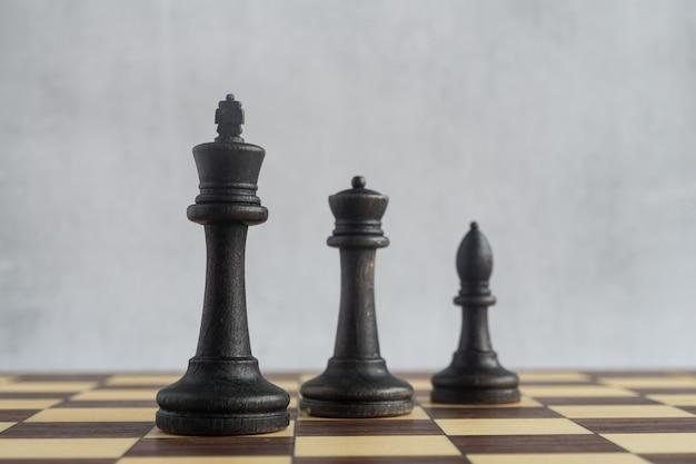 Rei preto rainha preta e bispo preto no tabuleiro de xadrez