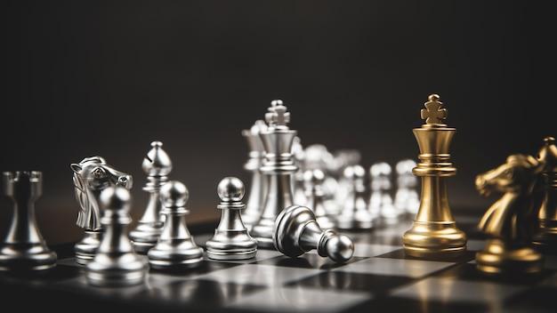 Rei xadrez dourado em pé de confronto da equipe de xadrez de prata.