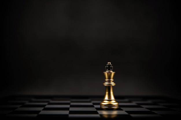 Rei xadrez dourado em pé no tabuleiro de xadrez