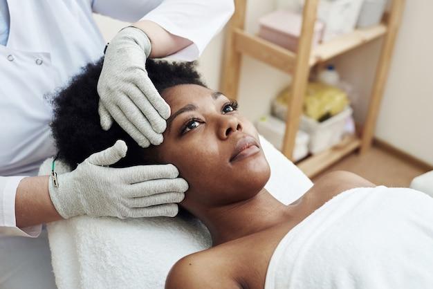 Rejuvenescimento facial com auxílio de terapia por microcorrentes. massagem de drenagem linfática. tratamento micro-sensorial elétrico bio ems de microcorrente